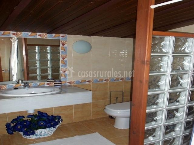 Baño con bonito cesto decorativo debajo del lavabo