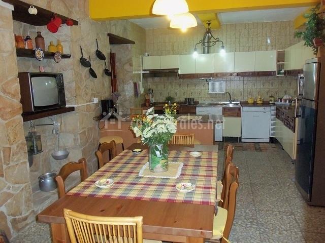 Mesa de comedor en la cocina, con televisión y decoración en las paredes