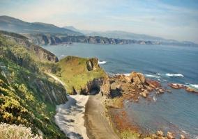 Vistas de la naturaleza: llanuras, montes al fondo, rocas modeladas por la acción del mar