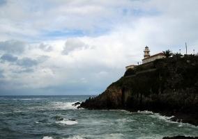 Faro mirando al mar, que golpea y modela las rocas