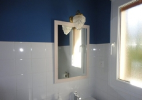 Aseo con pared de color azul y azulejos blancos