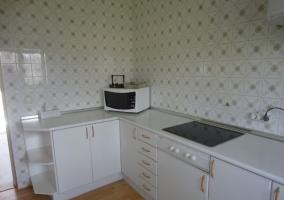 Cocina esquinada con muebles y encimera blancos y microondas