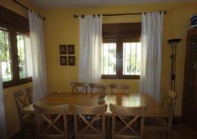 Comedor con mesa de madera y ocho sillas alrededor