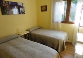 Dormitorio amarillo con dos camas individuales y cuadros de adorno