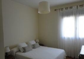 Dormitorio con cama blanca de matrimonio y mesillas