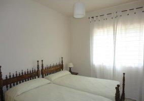 Dormitorio con dos camas individuales juntas y cabeceros adornados