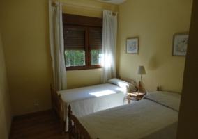 Dormitorio con dos camas individuales y visillo apartado