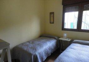 Dormitorio con dos camas y mesilla con lamparita