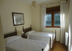 Dormitorio doble con cuadro colgado entre las camas