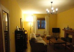 Lamparillas encendidas en el salón con sillón grande y muebles