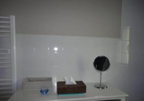 Mueble en el aseo con caja de clínex y un espejo redondo