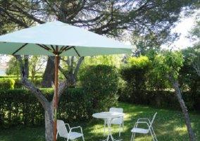 Muebles de exterior con sombrilla verde en zona ajardinada