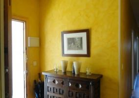Recibidor con paredes amarillas y mueble con cajones