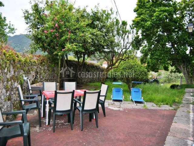 Patio exterior con mesas de jardín y hamacas