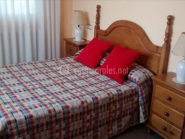 Dormitorio de matrimonio con detalles en color rojo y madera