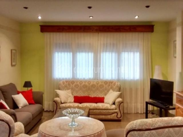 Sala de estar con sillones tapizados y televisor de plasma