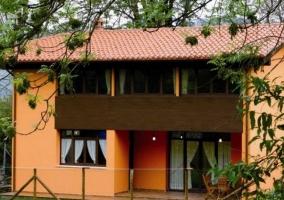 Acceso a la vivienda con espacios verdes y casa al fondo
