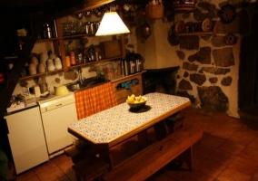 Cocina con menaje y mesa de madera