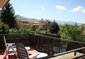 Terraza de la casa con tumbonas y vistas a la piscina