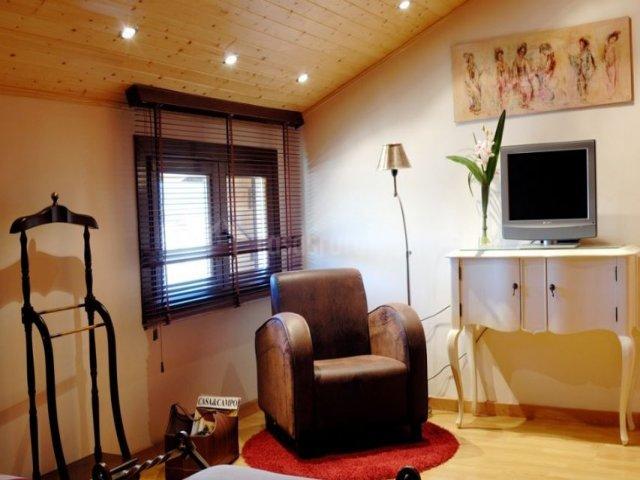 Dormitorio de matrimonio con butaca en tonos marrones