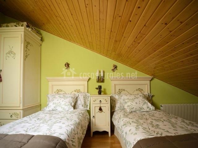 Dormitorio doble con mobiliario y techos en madera
