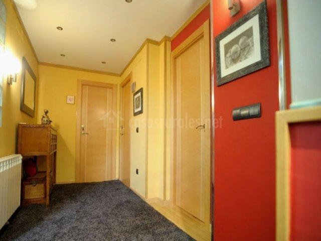 Pasillo con puertas de madera y paredes rojas