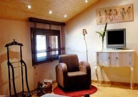 Dormitorio con sillones y televisor