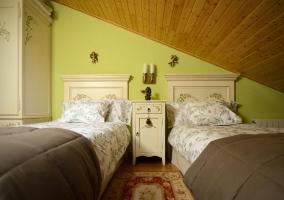 Dormitorio doble con mobiliario entre las camas