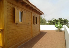 Fachada lateral de madera con muro blanco