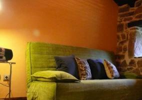 Sala de estar con sillones tapizados y paredes de piedras