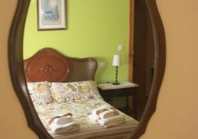 Dormitorio de matrimonio con juegos de toallas y espejo