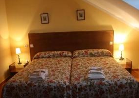 Dormitorio doble con colchas de flores y mesilla