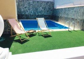 Mesa con sombrilla junto a la piscina