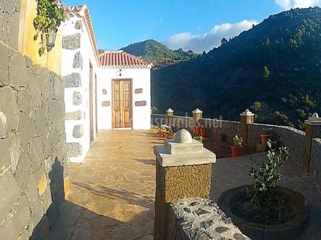 Vistas del patio abierto al entorno y puerta de la casa