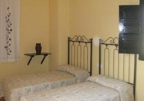 Dormitorio con camas individuales y cabeceros de forja