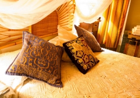 Cojines bordados sobre cama Espliego