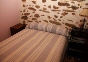Dormitorio de matrimonio con muro de piedra