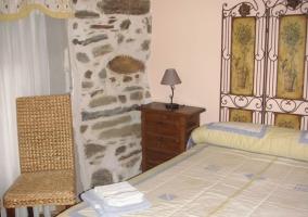 Dormitorio de matrimonio con original cabecero y silla