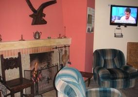 Sala de estar con sillones y chimenea de obra