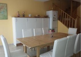 Cocina con mesa de madera junto a las escaleras