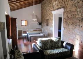 Salón y cocina con pared de piedra