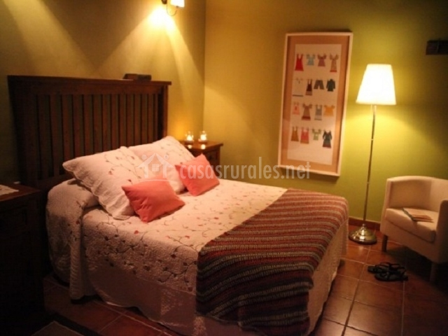 El dormitorio con la cama de matrimonio y cabecero de madera