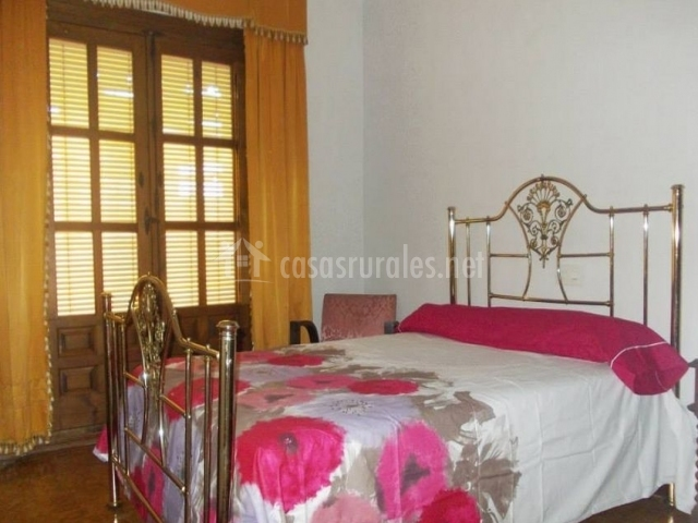 Dormitorio de matrimonio con colcha floral y balcón