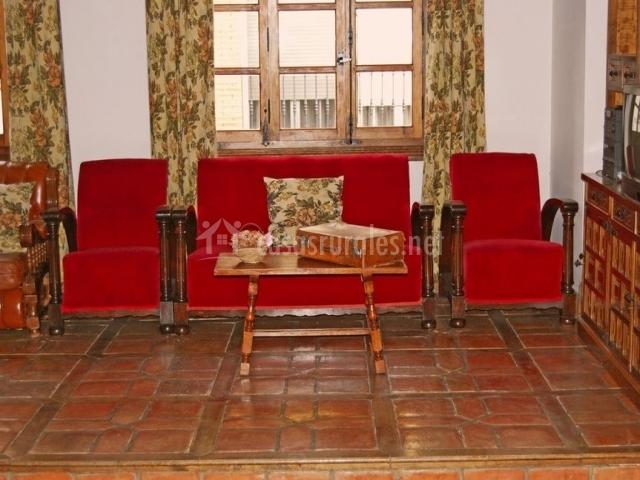 Salón comedor a doble altura con sofás en color rojo
