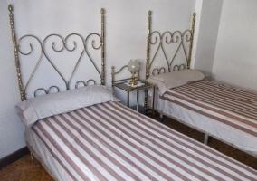Dormitorio con camas individuales y cabecero de forja
