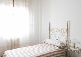 Dormitorio con camas individuales y colcha de rayas