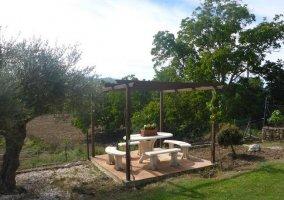 Mesa y bancos de piedra junto a la piscina