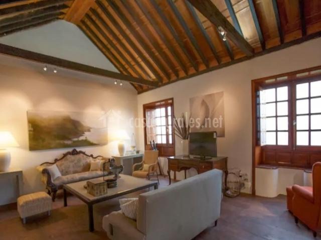 Sala de estar con sillones y techos de madera