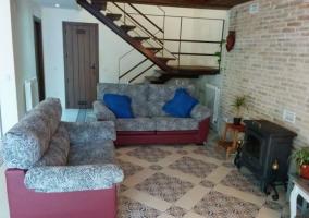 Sala de estar con la chimenea delante y escaleras
