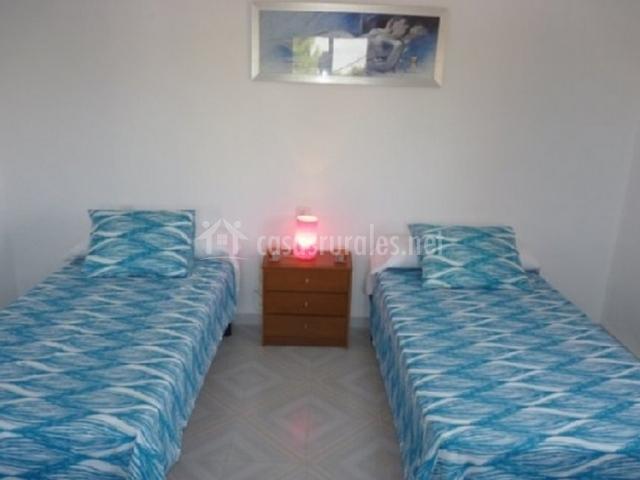 Dormitorio con dos camas individuales y mesilla en la casa rural